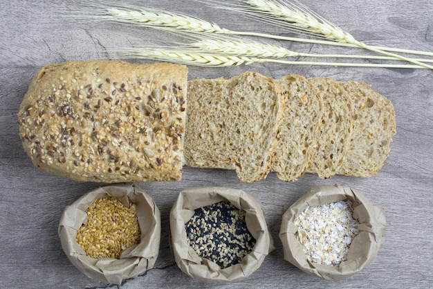 Sliced plain bread with weath, oat and seed on paper bags