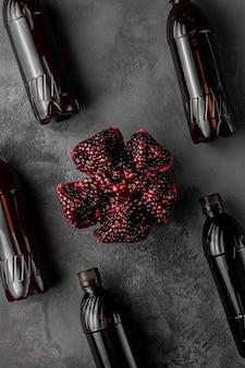 얇게 썬 석류 과일과 어두운 배경에 이국적인 음료가 든 많은 병, 위쪽 전망