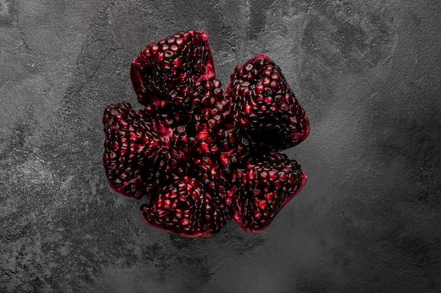 어두운 배경에 얇게 썬 석류 과일, 위쪽