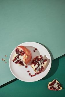 녹색 배경에 접시에 석류를 슬라이스. 평면 배치 및 복사 공간