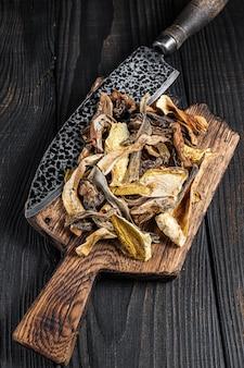 Нарезанные дикие сушеные грибы белые на деревянной разделочной доске