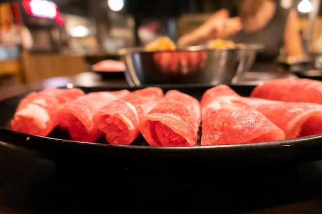 レストランの鍋用テーブルの皿にスライスした豚肉