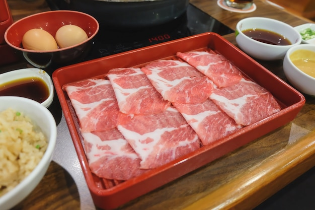Sliced pork serve on red plate for food concept sukiyaki (hot pot) & shabu.