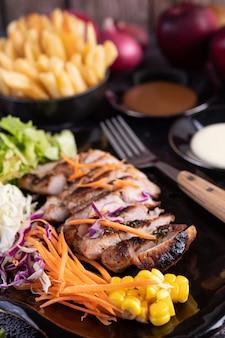 Sliced pork steak with bread, carrots, cauliflower, lettuce and corn on a black plate.