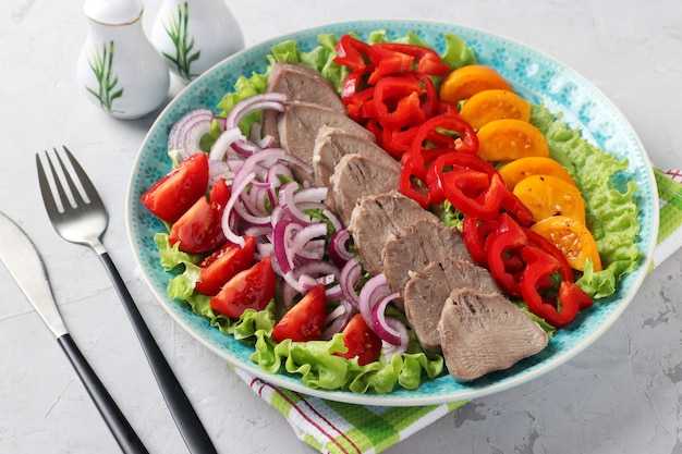 회색 배경에 파란색 접시에 야채와 함께 돼지 혀를 슬라이스. 차가운 전채. 수평 형식. 확대