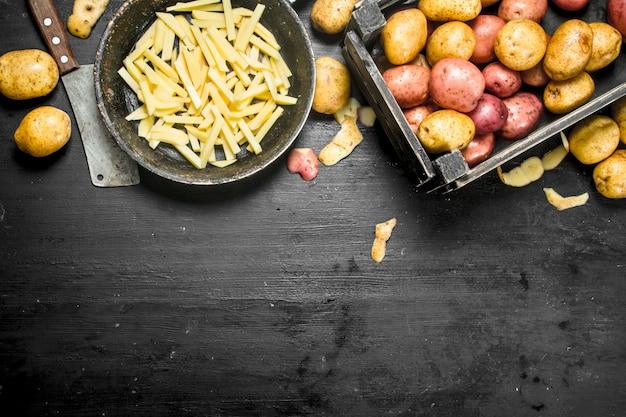 Нарезанный картофель на старой сковороде. на черной доске.