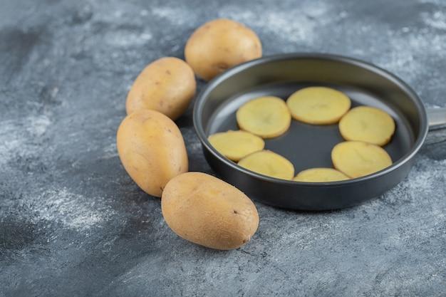 灰色の背景に鍋の内側にスライスされたジャガイモ。高品質の写真