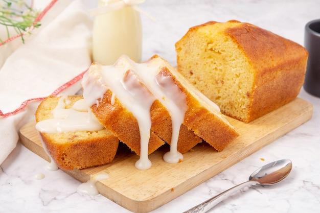 도마 위에 레몬 글레이즈를 얹은 슬라이스 파운드 케이크와 스푼은 대리석 테이블입니다.