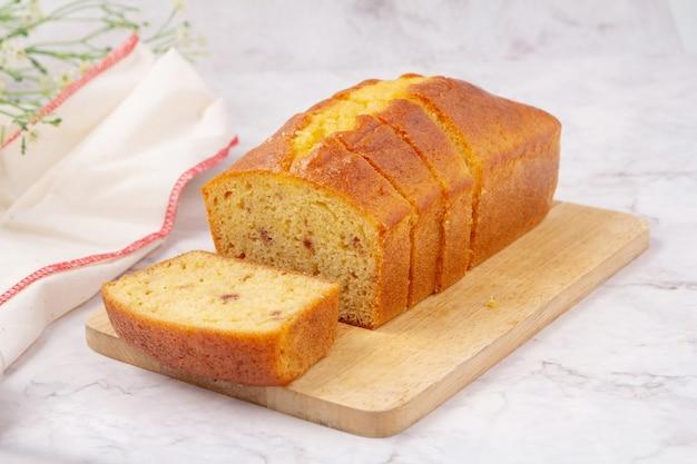 커팅 보드에 레몬 글레이즈를 얹은 얇게 썬 파운드 케이크.