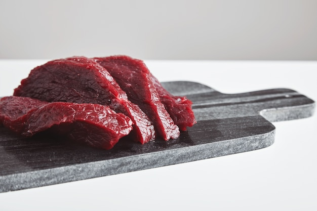 Sliced premium raw whale meat steak on marble stone cutting board isolated on white table. close up, side view