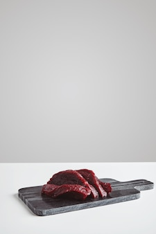 Sliced premium raw whale meat steak on marble stone cutting board isolated on white table