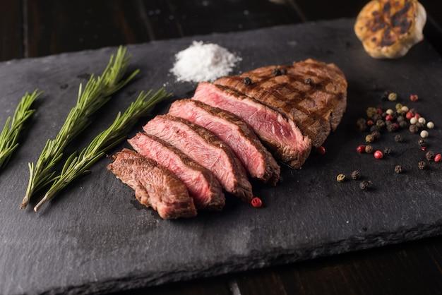 Нарезанный стейк рибай высшего качества на черной каменной тарелке. средняя степень прожарки стейка. с розмарином и перцем. вилка и нож.