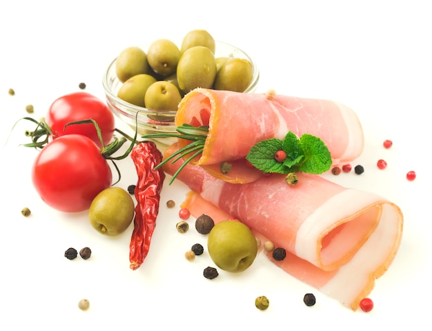 Sliced prosciutto with rosemary and olives on white