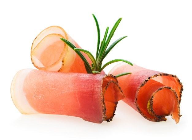 Sliced prosciutto with rosemary on white background