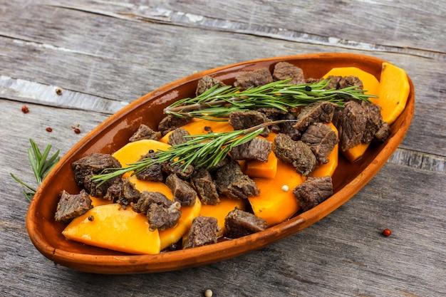 土鍋で肉を焼いたスライスしたカボチャ。ローズマリーとスパイスの秋の食事