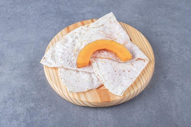 Zucca affettata sul gutap, sul piatto di legno, sulla superficie di marmo.