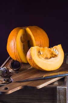 Sliced pumpkin; koelreuteria paniculata; chestnut with knife on wooden chopping board