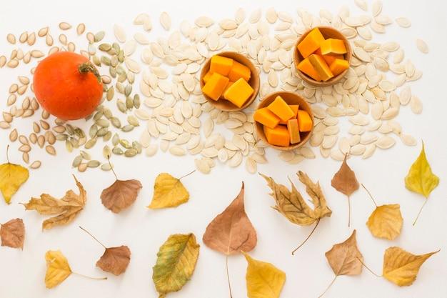 Нарезанные ломтики тыквы в деревянных мисках и семена на белом фоне
