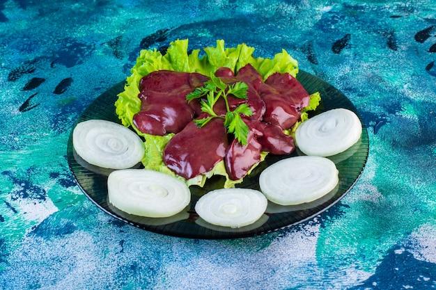 Нарезанный редис и субпродукты на листе салата на тарелке, на синем фоне