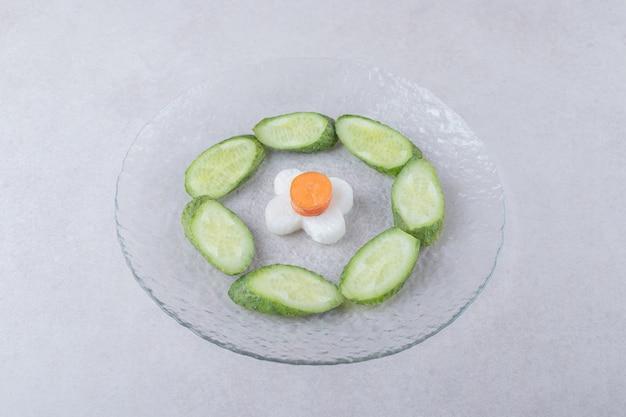 Нарезанный редис с морковью рядом с нарезанным огурцом на стеклянной тарелке на мраморном столе.