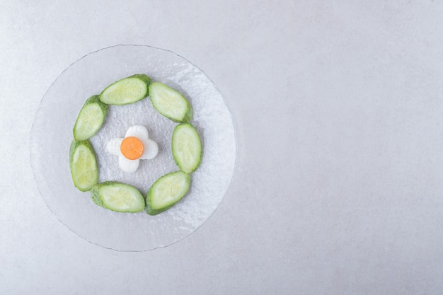 Sliced radish with carrot next to sliced cucumber on glass plate on marble table.