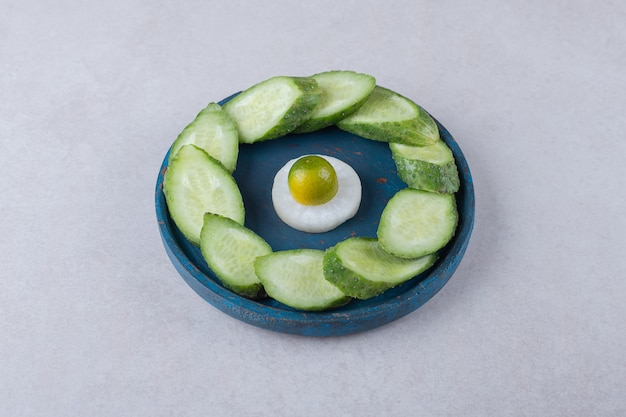Sliced radish with kumquat next to sliced cucumber on wooden plate on marble table.