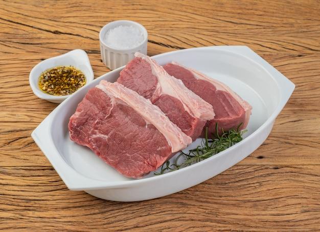 Нарезанная сырая говядина анчо, типичный аргентинский нарез, на белой тарелке с приправами.