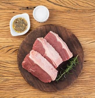 Нарезанная сырая говядина анчо, типичная аргентинская вырезка, на деревянной доске с приправами.