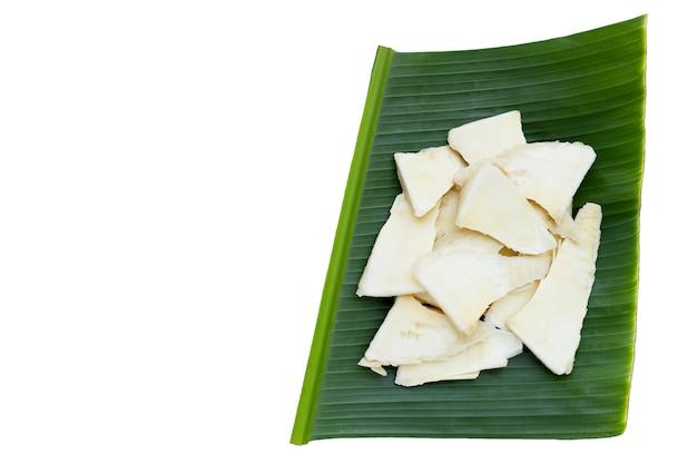白い背景のバナナの葉にスライスした生のタケノコ。