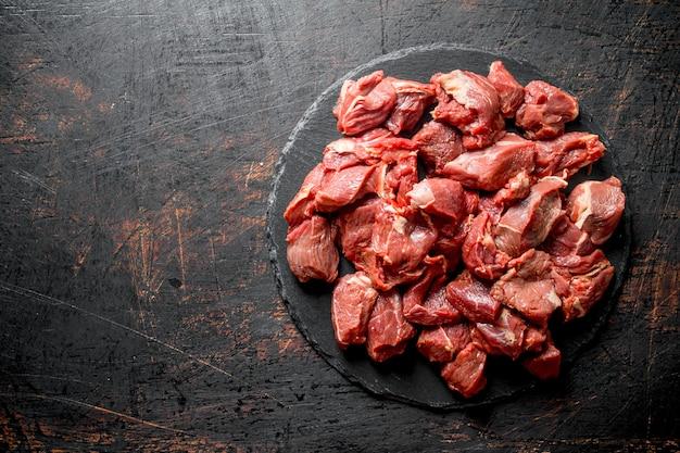 Sliced raw beef on a black stone board.