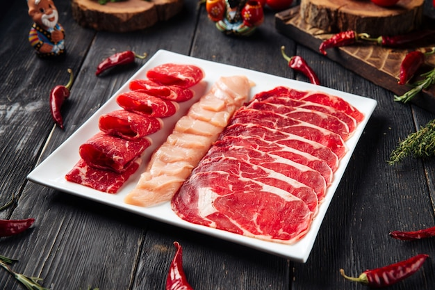 Sliced raw beef meat on the plate on the wooden surface