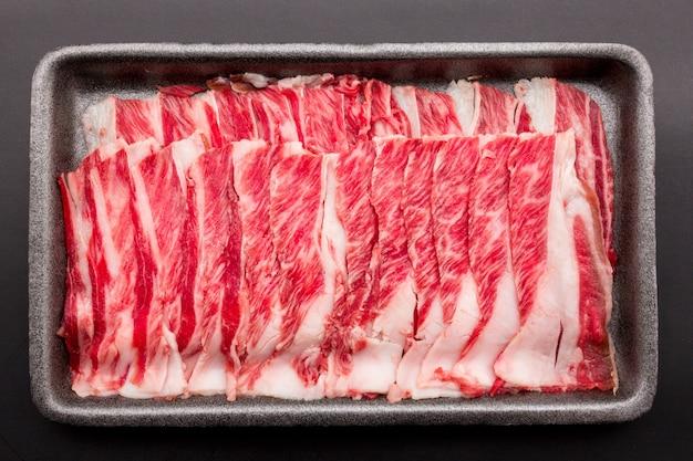 スライスした生の牛肉を、黒い背景で隔離された黒いプラスチックトレイに一列に並べます。スライスした料理用の肉、グリル用の新鮮な肉、焼肉、すき焼き、しゃぶ。
