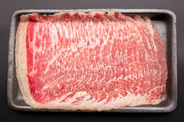 Sliced raw beef place in a row on a black plastic tray isolated on a black background. sliced meat for cooking, fresh meat for grilling, yakiniku, sukiyaki or shabu.