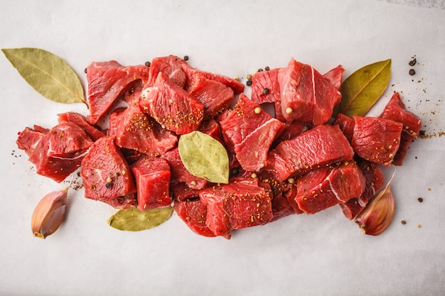 Sliced raw beef with spices on a white background, top view.