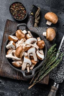 Нарезанные сырые грибы коричневые шампиньоны. черный фон. вид сверху.