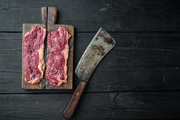 Sliced raw piece of marble beef steak, on black wooden table, top view flat lay
