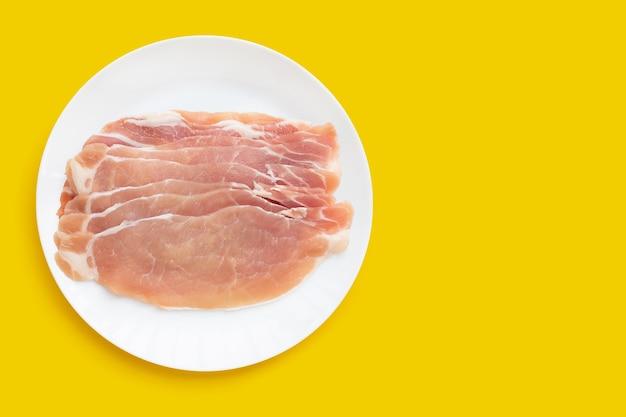 노란색 배경에 흰색 접시에 얇게 썬 생 돼지고기.
