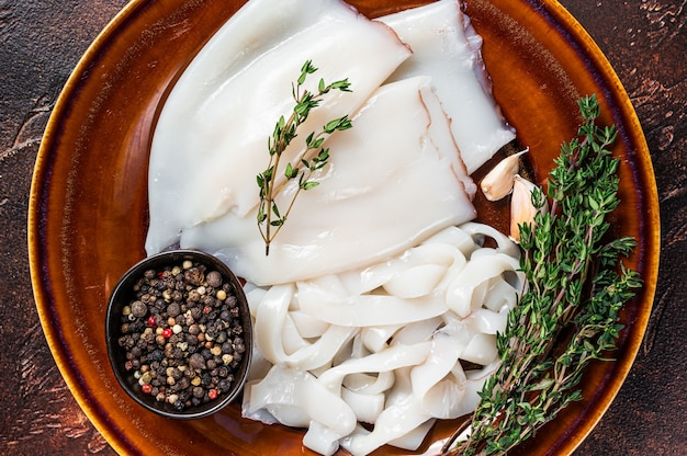 Sliced raw rings calamari in a rustic plate with rosemary. dark background. top view.