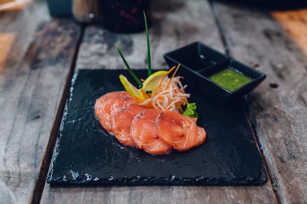 Нарезанный сырой лосось служил в качестве закуски. подается с тайским соусом.
