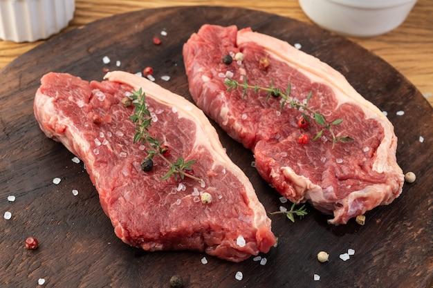 Нарезанное сырое мясо корейки на деревянной доске с приправами.