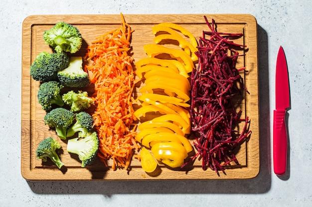 生野菜を木の板にスライスしました。生のブロッコリー、ピーマン、ニンジン、ビート、上面図。健康食品のコンセプトを調理します。
