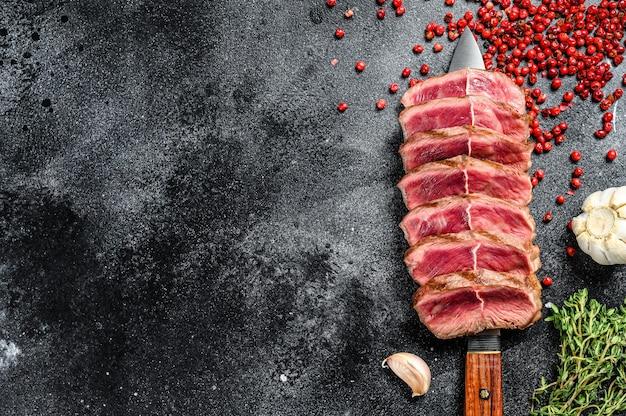 Нарезанный готовый к употреблению стейк top blade из говядины, мясо черного ангуса. черный фон. вид сверху. скопируйте пространство.