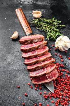 Нарезанный готовый к употреблению стейк top blade из говядины, мясо черного ангуса. черный фон. вид сверху.