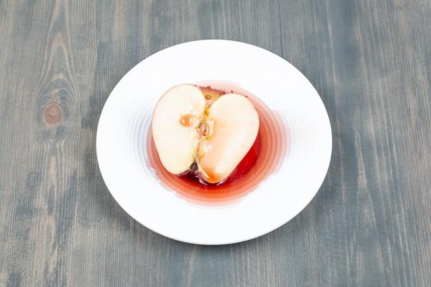 흰색 접시에 주스에 빨간 사과 슬라이스