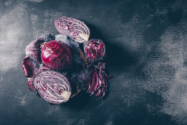 Sliced red cabbage on a dark textured background. top view.