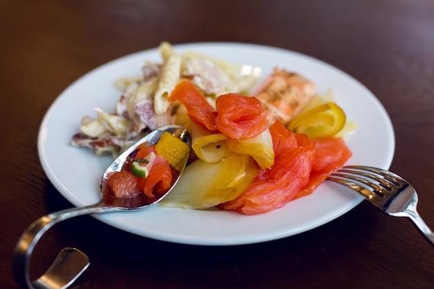 Нарезанная красная рыба на белой тарелке с изогнутой стальной вилкой и ложкой на деревянном коричневом столе