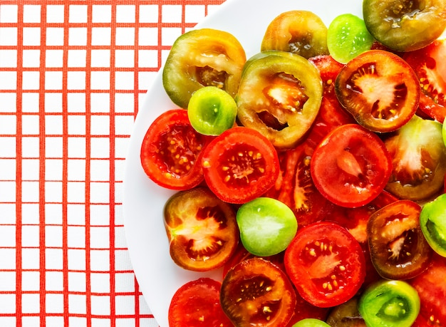 Sliced red, green and kumato tomatoes on white plate on red and white checkered tablecloth