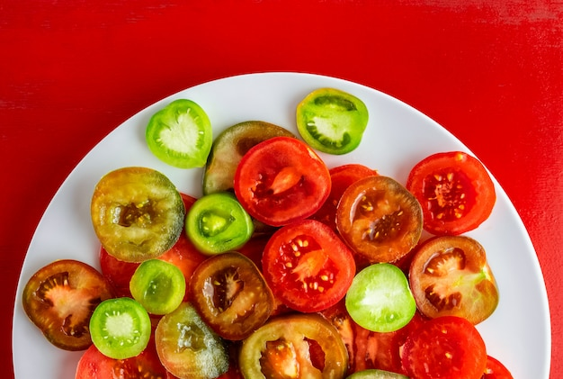Sliced red, green and kumato tomatoes on white plate on red wooden background