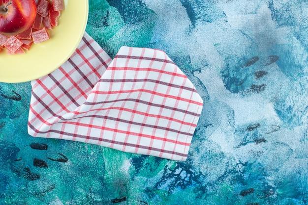 Нарезанный красный мармелад и яблоко в тарелке на кухонном полотенце на синем столе.