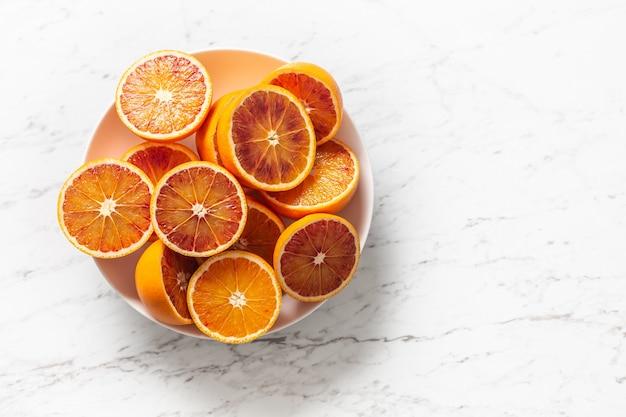 Нарезанные красные апельсины в тарелке на белом мраморном столе - вид сверху.